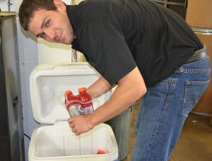 Brandon Sauder restocks a cooler with Gatorade to help keep employees of PBZ manufacturing hydrated.