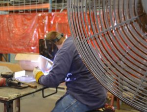 Matt Davenport works under hot conditions while a large fan provides some relief. Heat stress is a concern for those who work in job shops. Simple precautions, such as fans and coolers of water, can help prevent it.